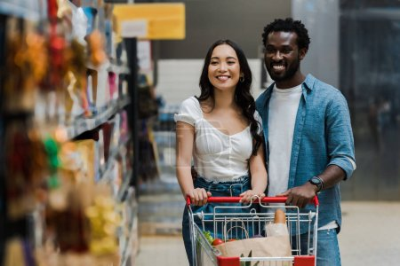 Photo for Selective focus of happy asian woman and cheerful african american man looking at shelves in supermarket - Royalty Free Image