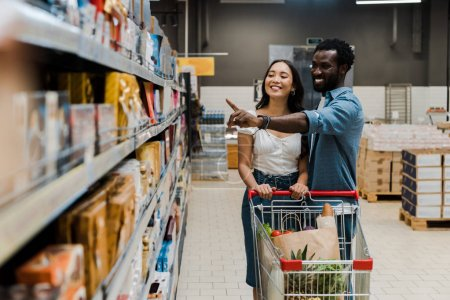 Photo for Selective focus of happy asian woman near cheerful african american man pointing with finger at shelves in supermarket - Royalty Free Image
