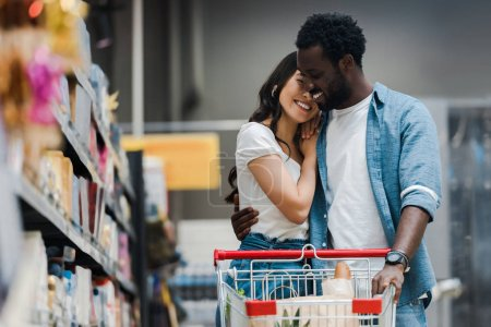 Photo for Selective focus of happy african american man hugging asian girl in supermarket - Royalty Free Image