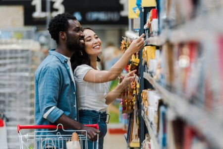 Photo for Selective focus of happy african american man standing with asian woman pointing with finger at groceries in supermarket - Royalty Free Image