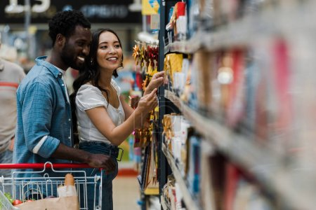 Photo for Selective focus of cheerful african american man standing with asian woman pointing with finger at groceries in supermarket - Royalty Free Image