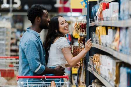 Photo for Selective focus of cheerful african american man standing with cheerful asian woman pointing with finger at groceries in supermarket - Royalty Free Image