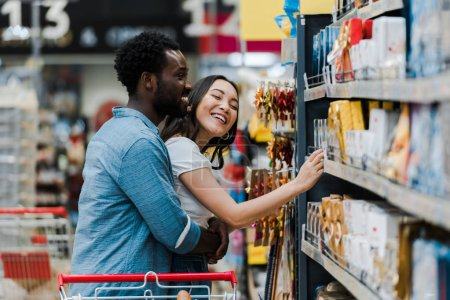 Photo for Selective focus of cheerful african american man standing with asian woman smiling near groceries in supermarket - Royalty Free Image