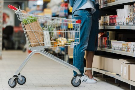 Photo for Cropped view of man standing with woman near shopping cart with groceries in supermarket - Royalty Free Image