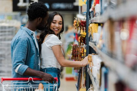 Photo for Selective focus of cheerful african american man standing with cheerful asian girl smiling near groceries in supermarket - Royalty Free Image
