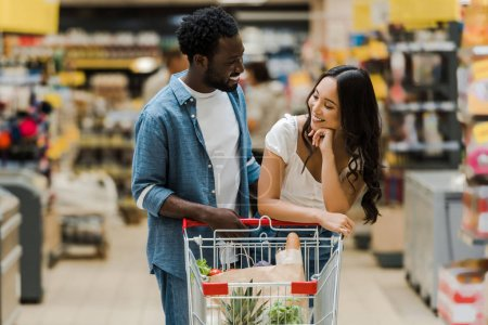Photo for Happy african american man looking at asian girl near shopping cart in supermarket - Royalty Free Image