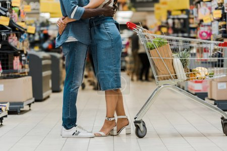 Photo for Cropped view of interracial couple hugging near shopping trolley with groceries - Royalty Free Image