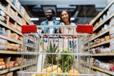 Photo for Selective focus of fruits in shopping cart near happy interracial couple in store - Royalty Free Image