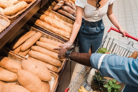 Photo for Overhead view of african american man pointing with finger at bread in supermarket - Royalty Free Image