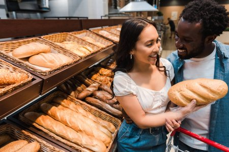 Photo for Happy asian woman holding bread near cheerful african american man - Royalty Free Image