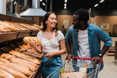 Photo for Happy asian woman holding bread near cheerful african american man standing with shopping cart - Royalty Free Image