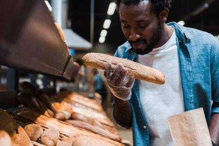 Photo pour Foyer sélectif de l'homme américain africain sentant le pain frais dans le supermarché - image libre de droit
