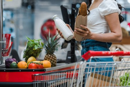 Photo for Cropped view of woman holding baguette and glass bottle with milk near supermarket counter - Royalty Free Image
