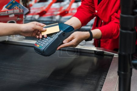 Photo for Cropped view of customer paying by credit card near cashier in supermarket - Royalty Free Image