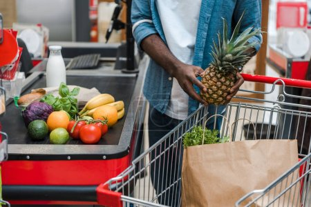 Photo for Cropped view of african american man holding pineapple near supermarket counter - Royalty Free Image