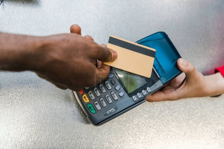 cropped view of african american man paying by credit card near cashier in supermarket