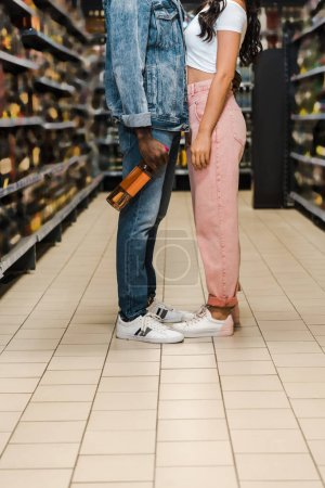 Photo for Cropped view of african american man holding bottle with wine near woman in supermarket - Royalty Free Image