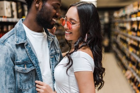 Photo for Happy african american man near cheerful asian girl in sunglasses - Royalty Free Image