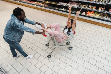 Photo for Overhead view of happy asian girl in sunglasses gesturing while sitting in shopping cart and looking at african american man - Royalty Free Image