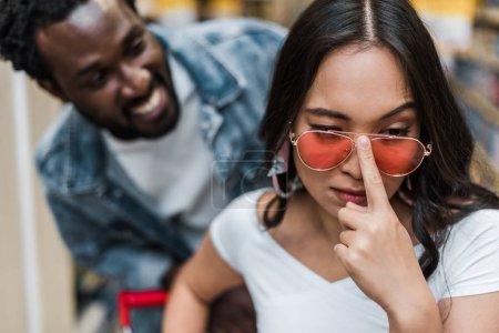 Photo pour Foyer sélectif de la femme asiatique touchant des lunettes de soleil près de l'homme américain africain heureux - image libre de droit