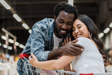 Photo for Happy african american man hugging asian pretty woman with closed eyes in store - Royalty Free Image
