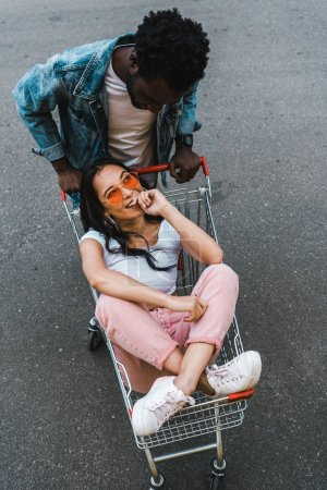 Photo for Overhead view of african american man looking at happy asian girl sitting in shopping trolley outside - Royalty Free Image