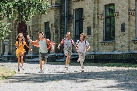 Foto de Cuatro adorables escolares multiculturales sonriendo mientras corría en el patio de la escuela - Imagen libre de derechos