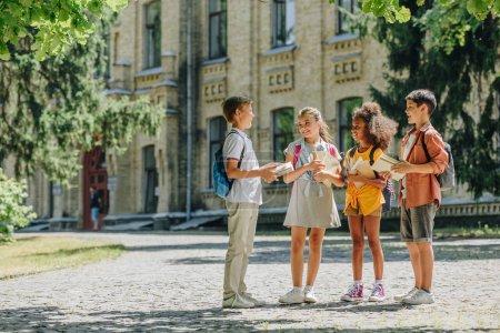 Photo pour Quatre écoliers multiculturels mignons parlant tout en restant dans la cour d'école et retenant des livres - image libre de droit
