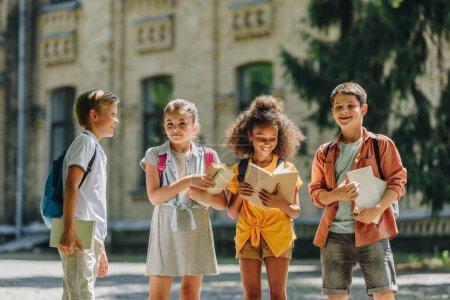 Photo pour Quatre adorables écoliers multiculturels debout dans la cour d'école et tenant des livres - image libre de droit