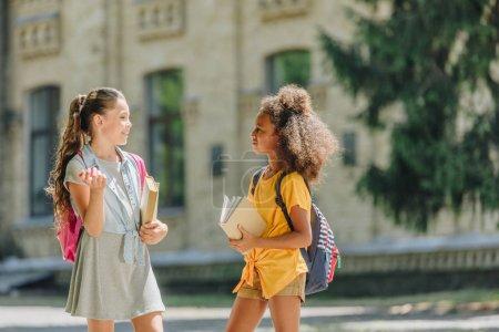 Foto de Dos alegres colegialas multiculturales sosteniendo libros y hablando en el patio de la escuela - Imagen libre de derechos