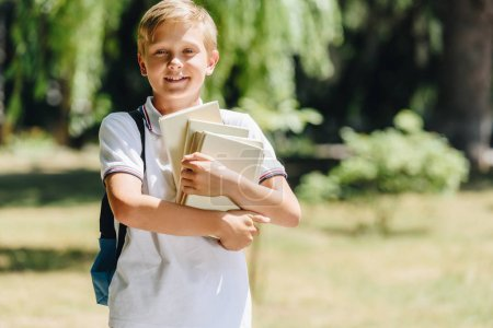 Photo for Adorable schoolboy with backpack holding books and smiling at camera - Royalty Free Image