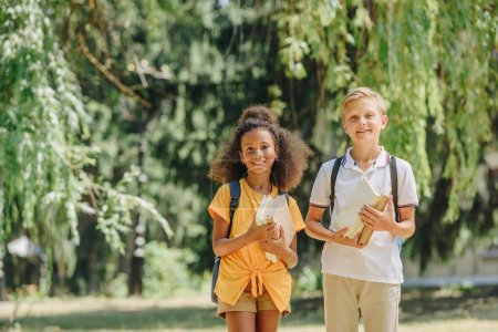 Foto de Dos alegres escolares multiculturales sonriendo a la cámara mientras sostiene na. libros - Imagen libre de derechos