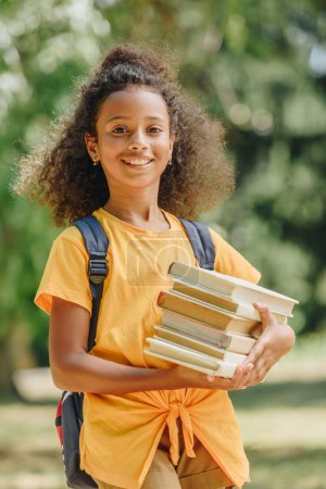 Photo for Happy african american schoolgirl holding books and smiling at camera - Royalty Free Image