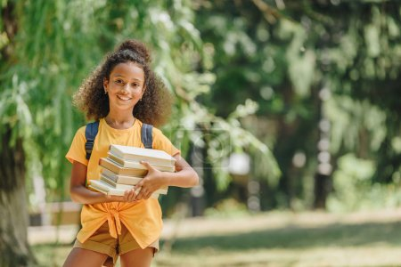 Photo for Cheerful african american schoolgirl holding books and smiling at camera in park - Royalty Free Image
