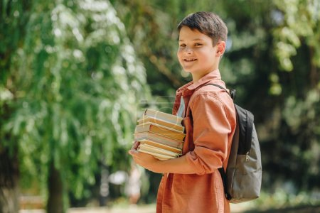 Photo for Happy schoolboy smiling at camera while standing in park and holding books - Royalty Free Image