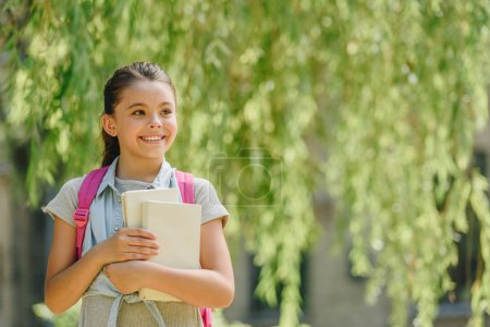 Photo pour Heureuse écolière regardant loin tout en se tenant dans le parc et tenant des livres - image libre de droit