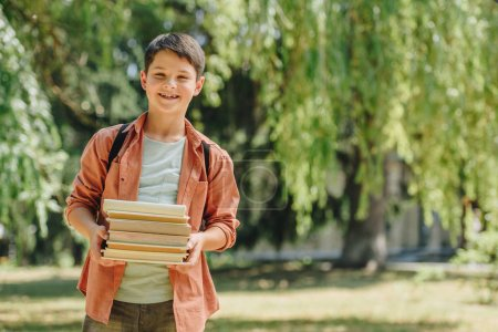 Photo for Smiling schoolboy looking at camera while standing in park and holding books - Royalty Free Image