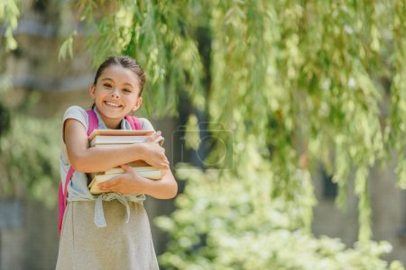 Photo for Adorable, happy schoolgirl looking at camera while holding books in park - Royalty Free Image