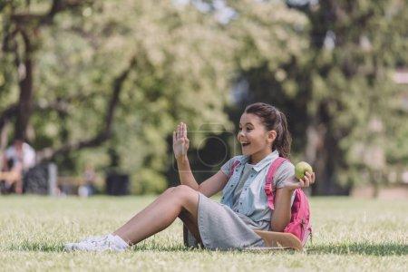 Photo pour Joyeuse écolière tenant la pomme et agitant la main tout en étant assis sur la pelouse dans le parc - image libre de droit