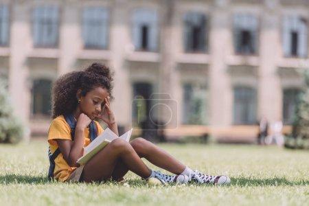 Photo pour Concentré afro-américaine écolière lecture livre tout en étant assis sur la pelouse - image libre de droit