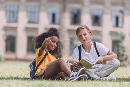 Foto de Alegre afroamericano colegiala mirando a la cámara y señalando con el dedo mientras está sentado en el césped cerca de amigo multiétnico - Imagen libre de derechos