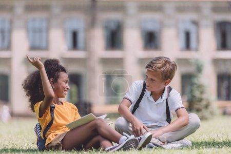 Foto de Alegre africano americano colegiala mostrando idea signo mientras sentado en el césped cerca multiétnico amigo - Imagen libre de derechos
