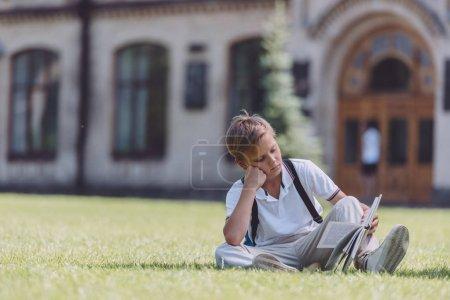 Photo pour Écolier attentif s'asseyant sur la pelouse près de l'école et du livre de lecture - image libre de droit