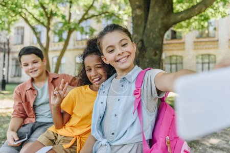 Photo for Cheerful schoolgirl taking selfie with multicultural friends while sitting on bench in schoolyard - Royalty Free Image