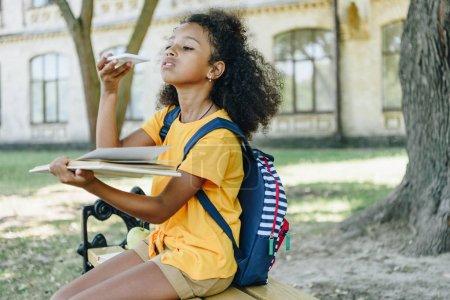 Photo pour Mignon afro-américaine écolière prendre des photos de livre avec smartphone tout en étant assis sur le banc dans le parc - image libre de droit