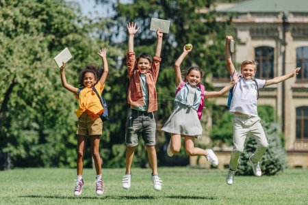Photo for Four excited multiethnic schoolkids jumping while holding books on lawn in park - Royalty Free Image