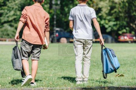 Photo pour Vue arrière de deux écoliers avec des sacs à dos marchant sur la pelouse en stationnement - image libre de droit