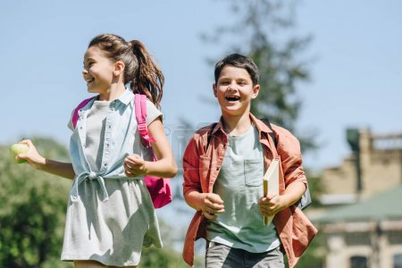 Photo for Two happy schoolkids with backpacks smiling while running in park - Royalty Free Image