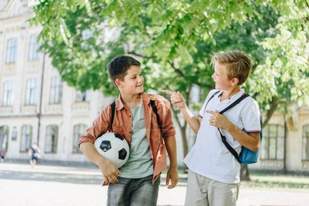 Photo for Two cheerful schoolboys with backpacks talking while walking in green park - Royalty Free Image
