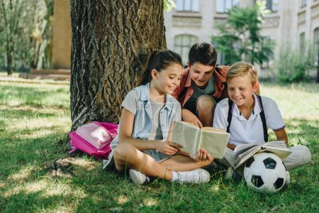 Photo for Three cute classmates reading book and smiling while sitting on lawn under tree - Royalty Free Image